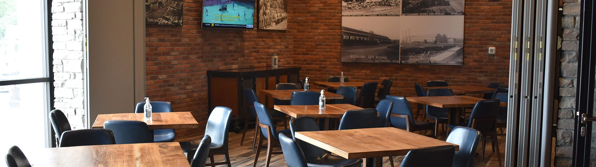 Dining tables with a TV showing a football game in the background.