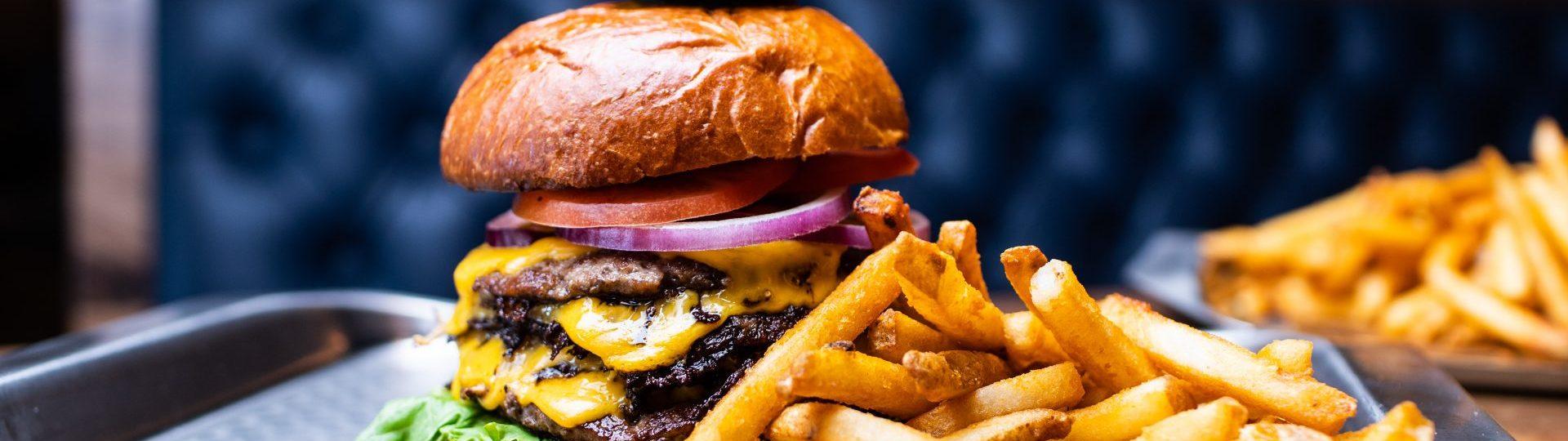 Tall hamburger with fries.
