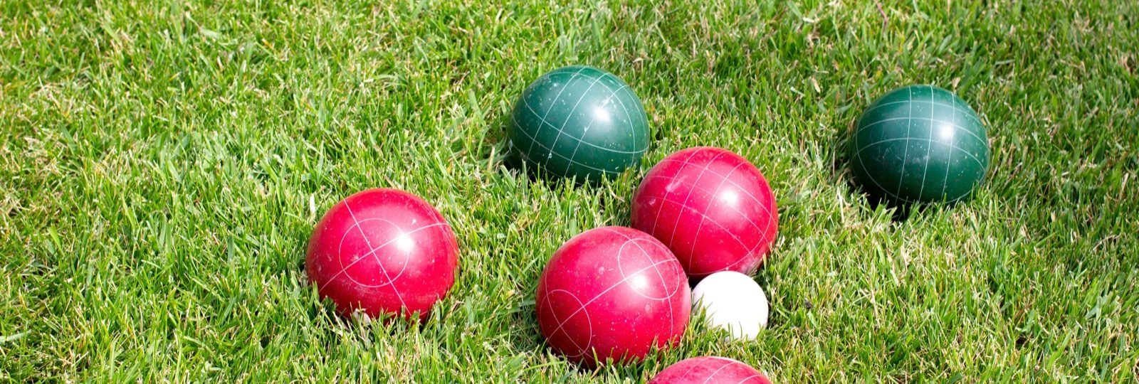 Red and green bocce balls lying in the grass.